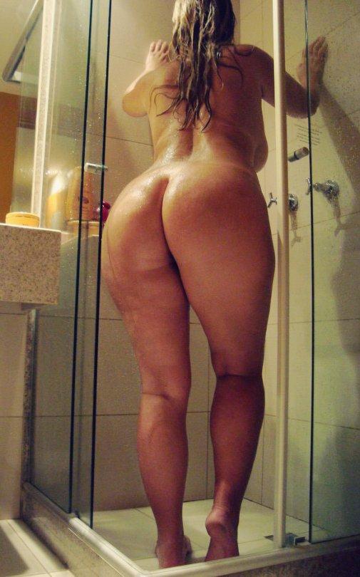 une femme ronde nue sous la douche